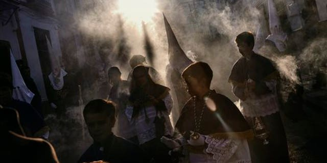 """Smoke of burning incense flows while penitents take part in the """"Estacion Penitencial de Nuestro Padre Jesus Nazareno Cautivo"""" Holy Week procession in Arriate, Spain, Thursday, April 2, 2015. Hundreds of processions take place throughout Spain during the Easter Holy Week. (AP Photo/Daniel Ochoa de Olza)"""