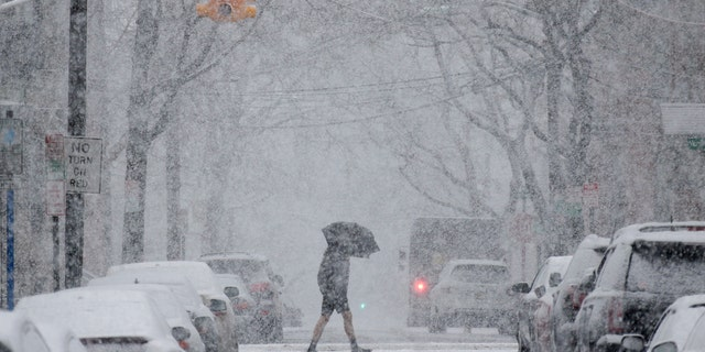 A man crosses the street through heavy snow in Hoboken, N.J., Wednesday, March 7, 2018.