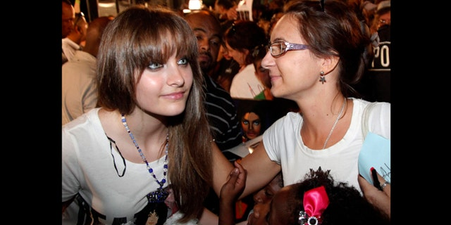 FILE - This Aug. 29, 2012 file photo shows Paris Jackson, left, daughter of the late pop icon  Michael Jackson, poses with a fan outside Jackson's boyhood home during a celebration on what would have been Jackson's  54th birthday in Gary, Ind. Jackson is physically fine after being taken to a hospital early Wednesday, June 5, 2013, an attorney for Jackson's mother said. Perry Sanders Jr. writes in a statement that Paris Jackson is getting appropriate medical attention and the family is seeking privacy.
