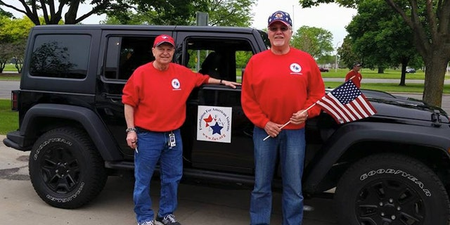 Foundation for American Veterans' Bob McDonald poses with flag (right)