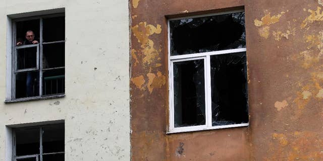 Sept. 24, 2014: A man observes the damage of a building after shelling in the town of Donetsk, eastern Ukraine. Mortar fire struck an apartment block in the rebel-held city of Donetsk overnight, yet another violation of a cease-fire declared weeks earlier between government forces and pro-Russian insurgents.