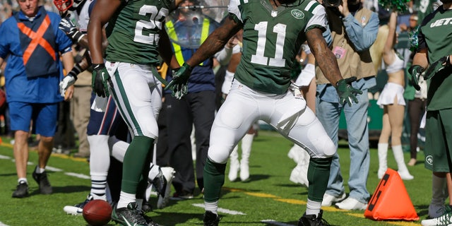 New York Jets wide receiver Jeremy Kerley (11) and Bilal Powell (29) celebrate a touchdown by Kerley during the first half of an NFL football game against the New England Patriots Sunday, Oct. 20, 2013 in East Rutherford.  (AP Photo/Seth Wenig)