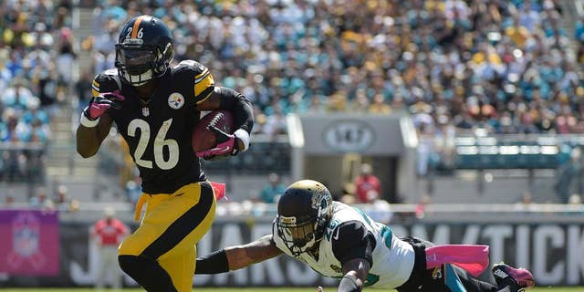 Pittsburgh Steelers running back Le'Veon Bell (26) breaks away from Jacksonville Jaguars strong safety Josh Evans, right, for yardage during the first half of an NFL football game in Jacksonville, Fla., Sunday, Oct. 5, 2014. (AP Photo/Phelan M. Ebenhack)