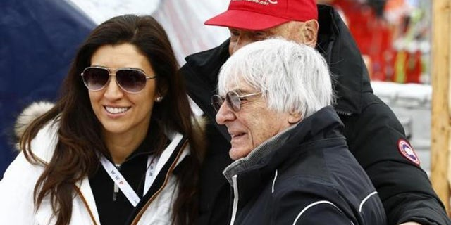 Fabiana Flosi (L) and Bernie Ecclestone (R), pose with Formula One champion Niki Lauda (rear)