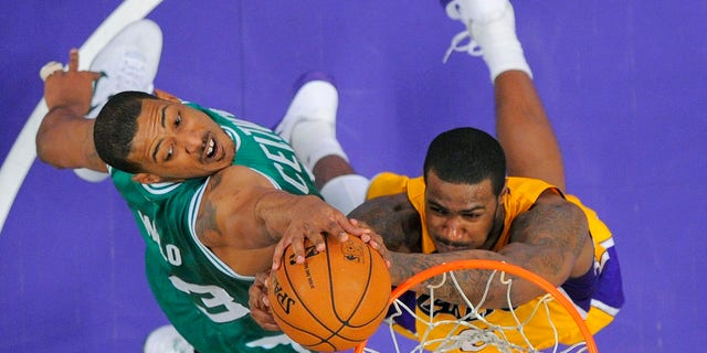 In this Feb. 20, 2013, file photo, Boston Celtics center Fab Melo, left, of Brazil, and Los Angeles Lakers forward Earl Clark go up for a rebound during an NBA basketball game in Los Angeles