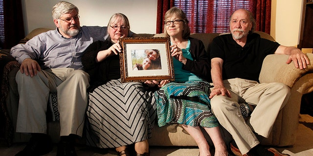 In this June 4, 2014, file photo, from left, Patrick Boyle, Linda Boyle, Lyn Coleman and Jim Coleman hold photo of their kidnapped children, Joshua Boyle and Caitlan Coleman, in Stewartstown, Pa.