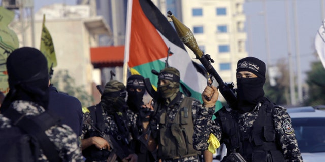 Masked militants from Nabil Masoud Brigades, a military wing of the Fatah movement, hold their weapons during a parade against Israeli arrangements in a contested Jerusalem shrine, along the streets of Gaza City, July 25, 2017.