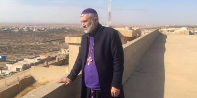 Christian leader Father Afram looks out at his once vibrant Christian town of Bahzani, Iraq outside of Mosul.