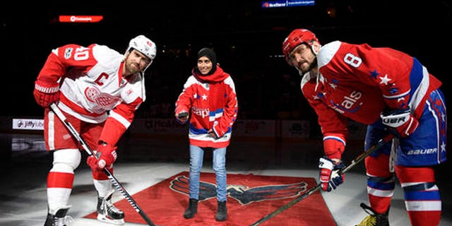Fatima Al Ali takes part in ceremonial puck drop Thursday with Alex Ovechkin (8) of the Washington Caps and Henrik Zetterberg of the Detroit Red Wings.