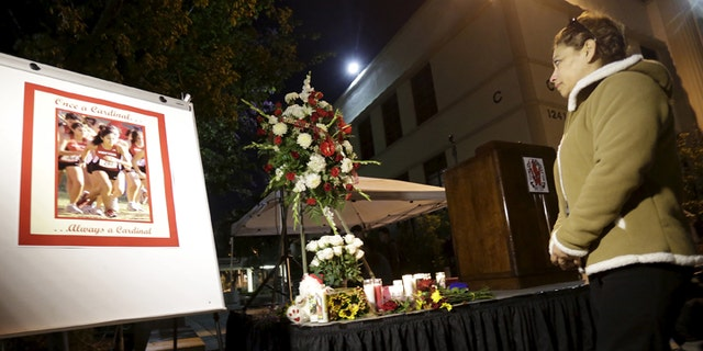 A woman stands at a makeshift shrine to honor Whittier High School alumna Nohemi Gonzalez, who was killed in the Paris terror attack last week, during a candlelight vigil in Whittier, California November 17, 2015. REUTERS/Jonathan Alcorn - GF20000064180