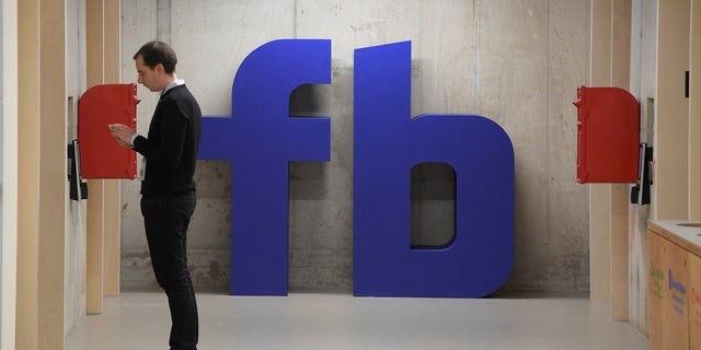A man waits for an elevator in front of a logo at Facebook's headquarters in London, Dec. 4, 2017.