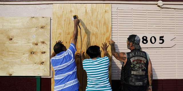 Richard Jay, left, and his wife Shanta get help from their tenant Anthony Perreria, right, as they board up their motel ahead of Hurricane Irma in Daytona Beach, Fla., Friday, Sept. 8, 2017. Coastal residents around South Florida have been ordered to evacuate as the killer storm closes in on the peninsula for what could be a catastrophic blow this weekend. (AP Photo/David Goldman)