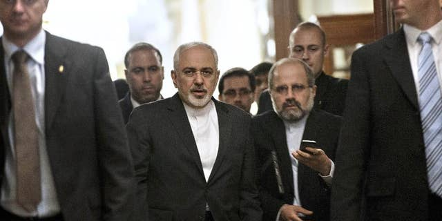 In this March 26, 2015, photo, Iranian Foreign Minister Mohammad Javad Zarif, center, leaves a meeting with U.S. Secretary of State John Kerry and other U.S. officials at a hotel in Lausanne, Switzerland. U.S. and Iranian diplomats gather at a Baroque palace in Europe, a historic nuclear agreement within reach. Over Iraq's deserts, their militaries fight a common foe. Leaders in Washington and Tehran, capitals once a million miles from each other in ideological terms, wrestle for the first time in decades with the notion of a rapprochement.  (AP Photo/Brendan Smialowski, Pool)