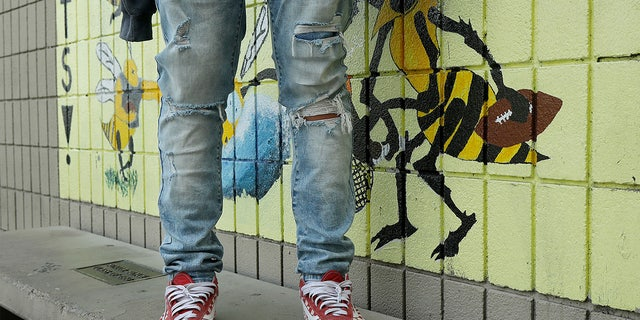 An Alameda High School student poses for photos wearing ripped jeans on the school's campus.