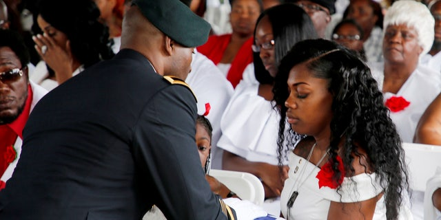 Myeshia Johnson, wife of U.S. Army Sergeant La David Johnson, receives the flag which draped his coffin at a graveside service in Hollywood, Florida