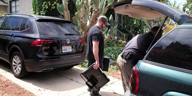 FBI agents remove evidence from the home of Robert Chain.