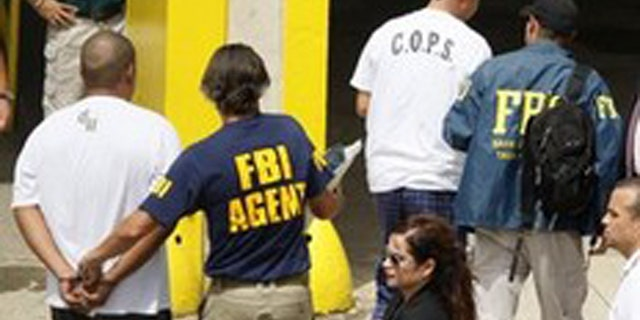 In this Oct. 6, 2010 file photo, FBI agents escort police officers and prison guards arrested in a major anti-corruption operation across the U.S. Caribbean  territory to the Puerto Rico Federal Court Building in San Juan.
