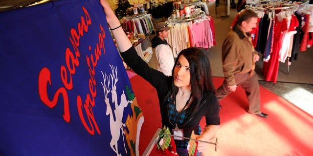 FILE: Transgender sales associate Mia TuMutch arranges a sign at the Castro Goodwill in San Francisco. A proposed California law will provide more protection for transgenders in the workplace and could allow for cross-dressing employees to wear whatever they want to work, despite workplace dress codes.