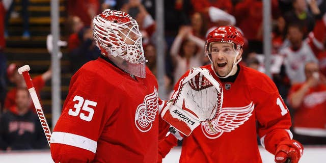 Detroit Red Wings goalie Jimmy Howard (35) celebrates with Detroit Red Wings center Pavel Datsyuk after beating the Carolina Hurricanes 3-2 in an NHL hockey game in Detroit Tuesday, April 7, 2015. (AP Photo/Paul Sancya)