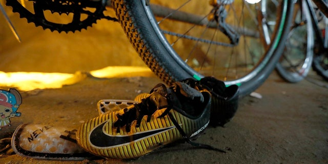 A pair of soccer shoes are left next to bicycles from a group of missing boys at the entrance of a deep cave in Chiang Rai, northern Thailand.