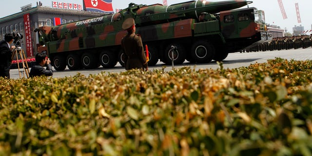 A North Korean vehicle purported to be carrying a new missile passes through a Pyongyang military parade.