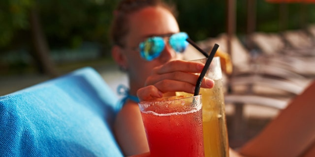 Couple clinking glasses with cocktails at poolside