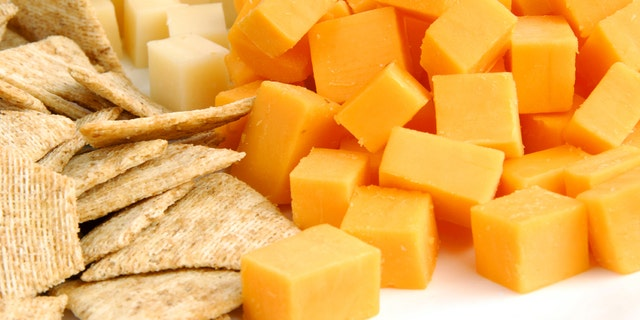 A party tray with swiss and cheddar cheese and crackers