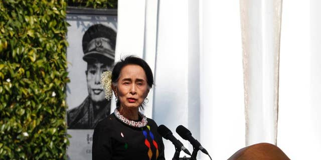Myanmar State Counsellor Aung San Suu Kyi, standing by a portrait of her late father and national hero Gen. Aung San and the Panglong monument, delivers a speech in Feb., 2017. (AP Photo/Thein Zaw)