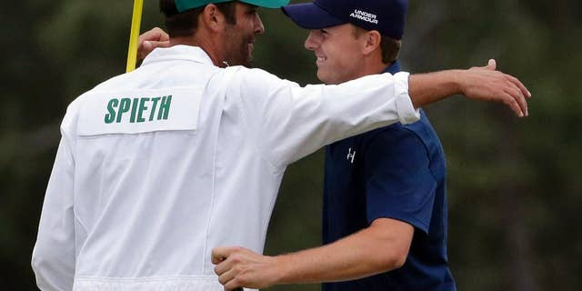 Jordan Spieth hugs his caddie Michael Greller after winning the Masters golf tournament Sunday, April 12, 2015, in Augusta, Ga.  (AP Photo/Chris Carlson)