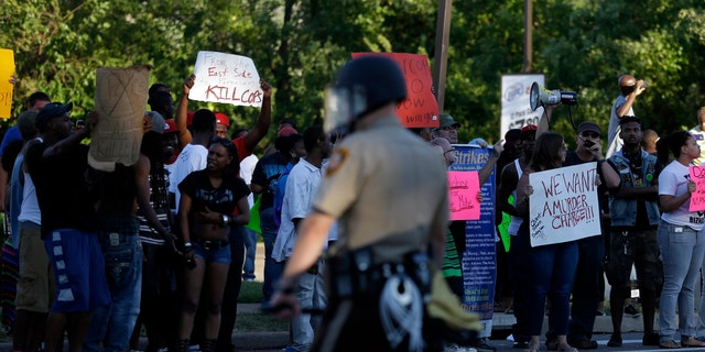 Aug. 12, 2014: Protesters line the street as police stand watch in Ferguson, Mo.