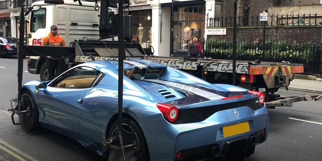 The truck operator had to strap the Ferrari to the four arms of the crane.
