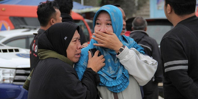 Relatives of victims of a sunken ferry weep as they wait for news on the search efforts.