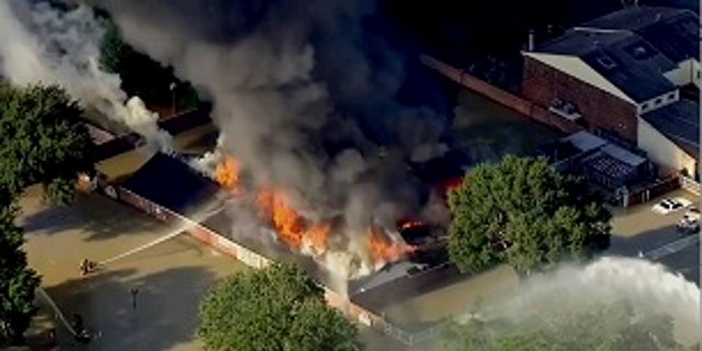Firefighters were battling a blaze at a Houston building surrounded by floodwaters.