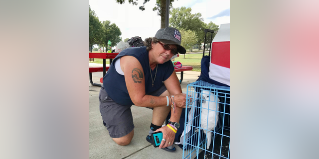 CORRECTS NAME TO LISA, NOT MELODY - Lisa Rawson looks over the possessions she grabbed from her first-floor apartment in Myrtle Beach, S.C., which are now spread out at a campground at the Atlanta Motor Speedway, and her two dogs and a cockatoo Wednesday, Sept. 12, 2018 in Hampton, Ga. She had a tire blow-out in her minivan before arriving around 3 a.m. Wednesday at the speedway, which has invited hurricane evacuees to stay at its vast campgrounds. (AP Photo/Jeff Martin)