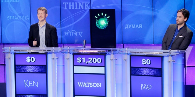 """""""Jeopardy!"""" champions Ken Jennings, left, and Brad Rutter, right, look on as an IBM computer called """"Watson"""" beats them to the buzzer to answer a question during a practice round of the """"Jeopardy!"""" quiz show in Yorktown Heights, N.Y., Thursday, Jan. 13, 2011."""