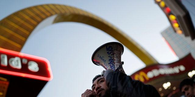 A protestor speaks on a bullhorn as he and others protest near a McDonald's restaurant along the Las Vegas Strip, Tuesday, Nov. 29, 2016, in Las Vegas. The protest was part of the National Day of Action to Fight for $15. The campaign seeks higher hourly wages, including for workers at fast-food restaurants and airports.