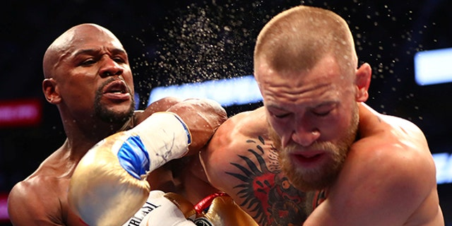 Floyd Mayweather Jr. lands a punch against Conor McGregor during their boxing match in Las Vegas, August 26.