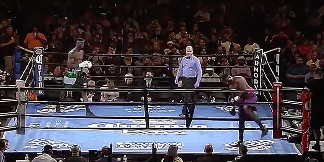 Curtis Harper, bottom right, walks out of the ring, seconds after touching gloves with Efe Ajagba.