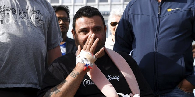 Hassan Zubier, who was injured in a mass stabbing in Finland, wipes his face as he visits Turku Market Square.