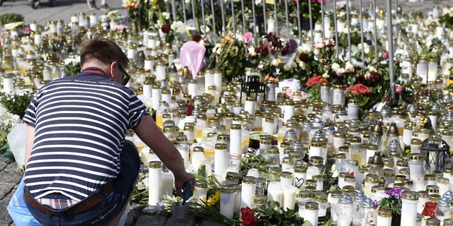 A person lights a candle in Turku Market Square, Finland, Sunday Aug. 20, 2017, as a memorial for the victims of Friday's stabbings in Turku.