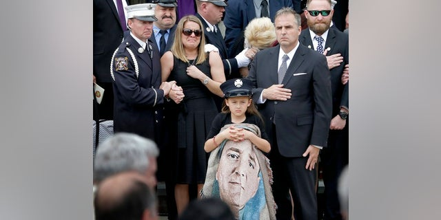 Isabella Tolley, 8, holding a blanket with a picture of her father.