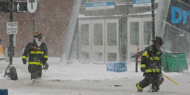 Boston firefighters wading through a street flooded from tidal surge.