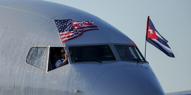 TOPSHOT - An American Airlines plane fluttering US and Cuba national flags is seen uppon arrival at Jose Marti International Airport becoming the first Miami-Havana commercial flight in 50 years, coinciding with the beginning of the tributes to late Cuban leader Fidel Castro, on November 28, 2016 in Havana.  / AFP / YAMIL LAGE        (Photo credit should read YAMIL LAGE/AFP/Getty Images)
