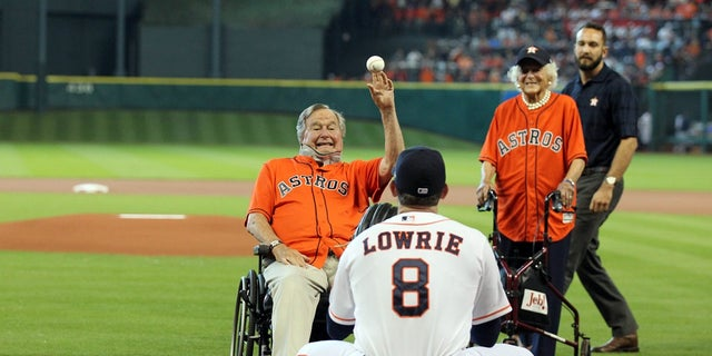 Former President George H.W. Bush throws out the ceremonial first pitch to the Houston Astros in a game against the Kansas City Royals in 2015.