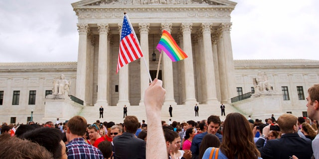 June 26, 2015: A man holds a U.S. and a rainbow flag outside the Supreme Court in Washington after the court legalized gay marriage nationwide. (AP)