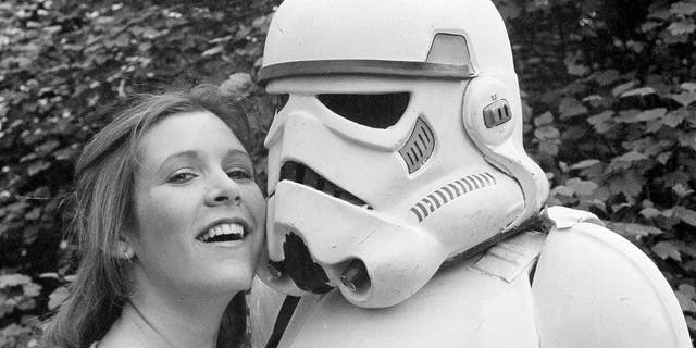 Actress Carrie Fisher hugs a person dressed as a stormtrooper in London in 1980.