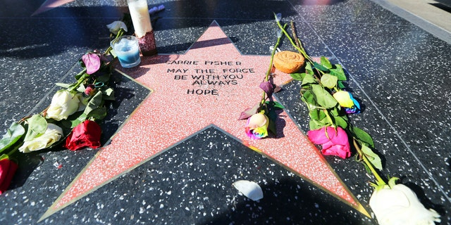 Flowers and candles dot an impromptu star on the Hollywood Walk of Fame for Carrie Fisher