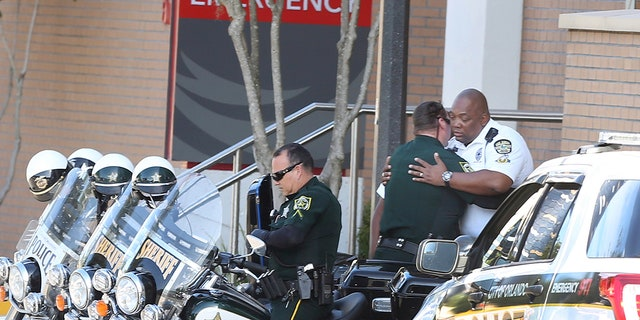 A Orange County Sheriff Motor deputy,center, gives support to a Orlando Police Motor officer,right, at Orlando Regional Medical Center after a OPD officer was shot and severely injured while responding over night to a domestic dispute call.