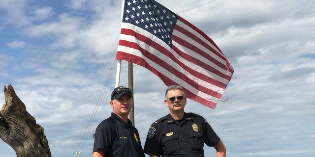 Officers Captain Ashley Brown, left, and Lt. Greg Ernst stand next to the American flag they rescued on Patriots Day.