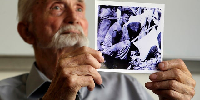 WWII veteran Marvin Strombo holds up a photo of himself taken during the battle on Saipan.